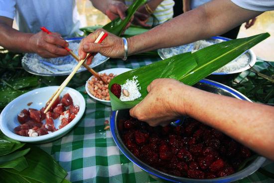 二、包粽子   泰宁端午还有送节习俗,女婿订婚后及结婚前三年,在端午节前几天,要向岳父母家送粽子、猪肉、粉干等礼品,因此粽子的制作一般会提前两三天。   泰宁粽子与传统做法并无差别,将糯米浸泡发涨,掺入草木灰碱,用竹叶包裹起来再用棕榈叶的丝缠扎,最后入锅煮7小时左右。熟后,色泽金黄,芬香扑鼻,而且能保存较长时间不霉变。富裕人家,会做一些在糯米中掺入红米豆、黑豇豆或猪肉的粽子。有意思的是在包粽子时,父母长辈一般会做几个更细更长更小的羊角粽,在端午这天给小孩与香包挂在胸前,以避瘟驱邪。吃粽子时,一