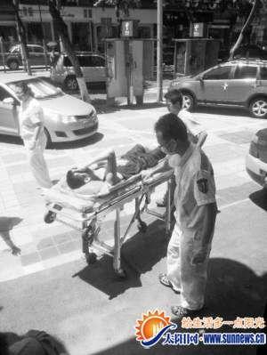 腿部受伤男子被抬上担架。记者 倪立婧 摄