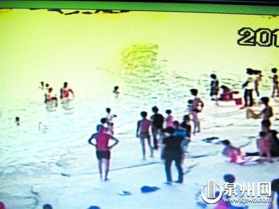 画圈处,冬泳队员抱着落水的男孩走上岸(监控截屏)