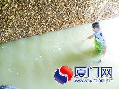 法医姚博站在齐腰深的水里打捞尸块。
