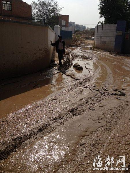 路面泥泞,居民进出自带塑料袋当鞋套