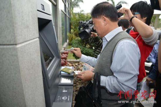 """台湾黄先生正在""""24小时自助受理机""""前提交申请并缴费"""
