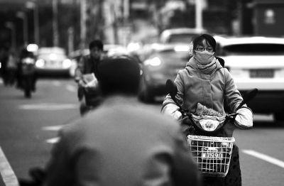 东泰路,骑车出行的市民带上了口罩和手套