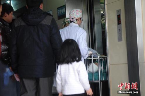 12月16日,重庆儿童医院,原原的家属已经守候在重症监护室外,等待孩子推出监护室。重庆长寿区被摔男婴原原进行开颅手术。图为医生将原原推进电梯。陈超摄