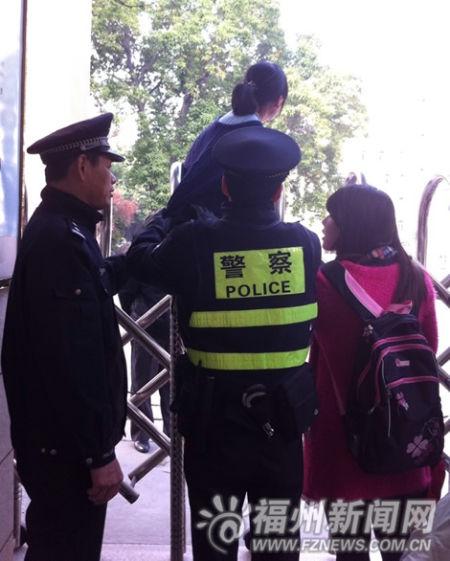 女生欲翻门进入考场,被民警劝住。
