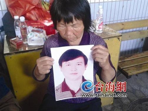 苏明宝的母亲拿着儿子的照片,一脸悲伤
