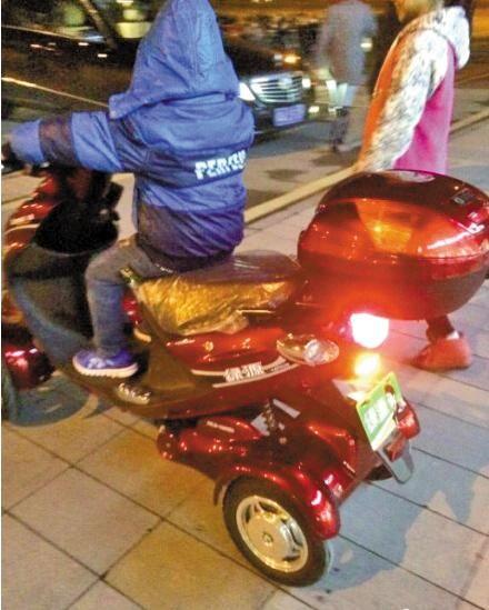 """""""土豪""""小男孩正骑着电动车,旁边站着""""女友""""(网图)"""