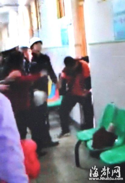 一名保安用头盔(画圈处)往卓先生的头上敲(视频截图)