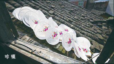 描上画的油扇被放在屋顶晾晒