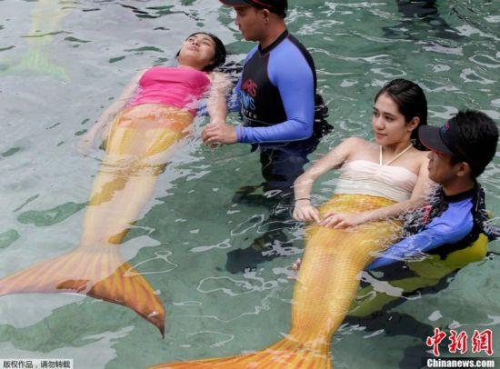"""当地时间2014年4月11日,菲律宾马尼拉,教员帮助身着""""美人鱼""""服装的学员学习在水中漂浮。"""