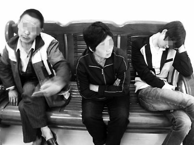 老杨在与民警交流,小杨靠在派出所椅子上睡着了