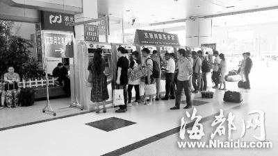 火车站取票机前,旅客正排队取票