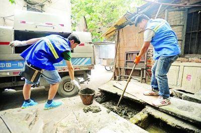 """五福路一老社区里,""""80后""""的王轩在疏捞堵塞的粪池。记者苗剑 摄"""