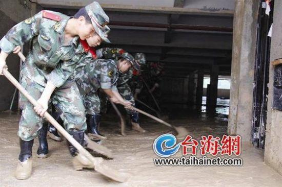 ▲武警三明支队官兵暴雨后在泰宁县街头清淤