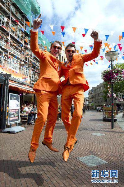 """最""""fashion"""" 6月23日,荷兰球迷在鹿特丹市中心庆祝荷兰队获得小组头名出线。当日,在巴西圣保罗伊塔盖拉球场进行的2014年巴西世界杯小组赛B组比赛中,荷兰队以2比0战胜智利队,并以3战3胜积9分的成绩获得小组第一,晋级16强。  新华社发(罗宾·于特雷西特摄)"""
