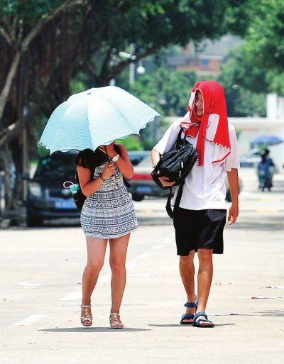 连日的暴雨突然销声匿迹,酷日悄悄降临。一位撑伞的姑娘和披着毛巾的男子在街头走着 东快记者刘兴/摄