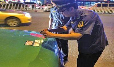 执法人员对违章车辆进行登记