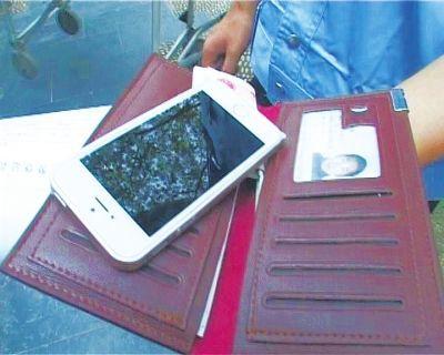 """男子被控制后,民警从其身上找到一个高档钱包,一部最新的苹果5S""""土豪金""""手机"""