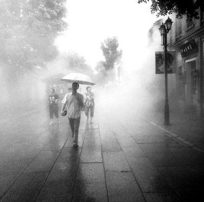 昨天早上的雨后,几名游客穿过南后街人工喷雾路段。许艺民/图