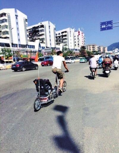 福州奶爸自行车后挂推车遛孩子 网友认为不安全