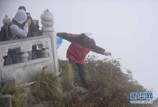 彭文才在金顶护栏外的悬崖上捡垃圾。新华社记者 薛玉斌 摄