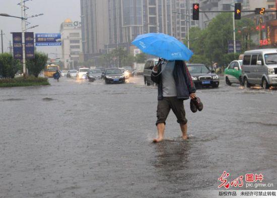 2013年5月8日,在江西九江市柴桑路,一市民手提皮鞋赤足穿过水淹道路。