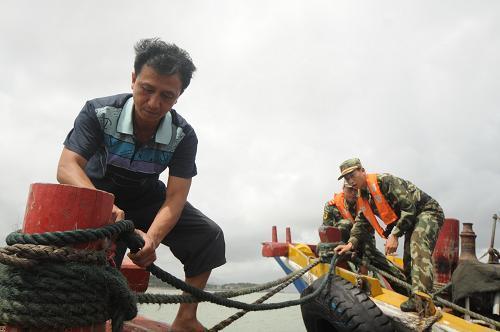 6月10日,武警战士在帮助渔民收好渔具。