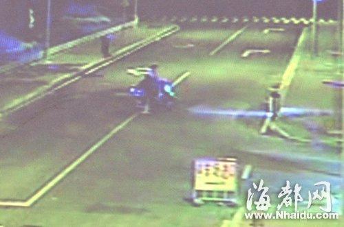 摩托车后座的男子俯下身,捡起倒毙在地的小狗