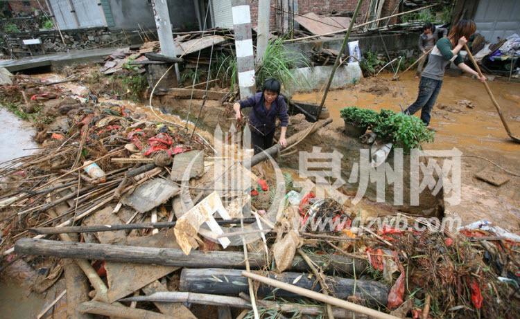12日上午,在省道307线白濑乡附近路段的村民在清理暴雨带来的垃圾。