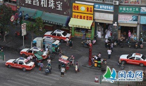 温陵南路城雕附近,四辆的士并排挤在非机动车道和人行道