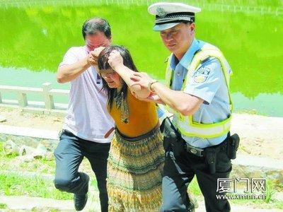 民警和协警将这名女子扶上警车带回派出所。