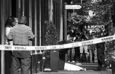 8月24日,纽约帝国大厦附近发生枪击案,一名死者躺在地上,周围有围观的群众和电视台记者。