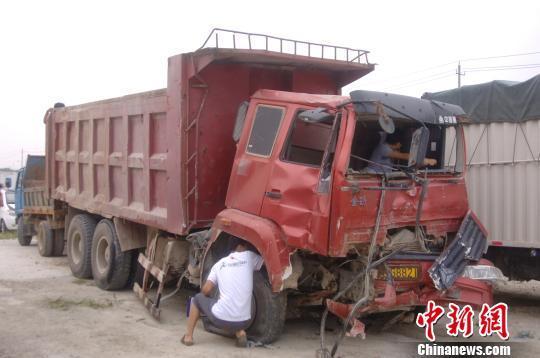 8月29日,福建晋江龙湖镇镇政府门口的灯控路口,一辆满载土石的重型货车撞上同向行驶正在等待绿灯的一辆小轿车并将其压扁,造成小轿车上4人全部死亡。图为肇事的大货车。 陈龙山 摄