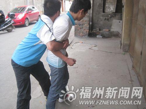 参与追小偷的高先生和练先生演示当时高明聪紧紧抱住窃贼的情景,地面上还有干透的血迹。