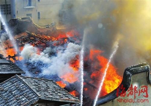 凶猛的大火从老房子中蹿起,威胁周围的木屋区,两条水龙冲天而起喷向大火