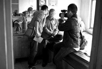 14日,莫言90岁的父亲管贻范在接受记者采访,由于听力不好,记者凑到老人的耳边说话。新京报记者 陈杰摄