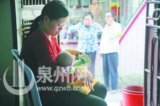 魏某妻子怀抱女儿在家门口求助乡亲施舍