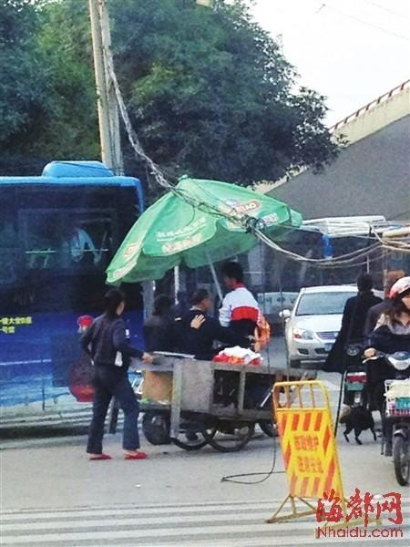 少年巧用遮阳伞,撑起低垂线缆,公交车得以顺利通行(市民王女士供图)