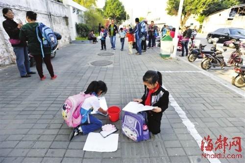 爸爸妈妈怎么还不来?她们就蹲在路边边做作业边等待