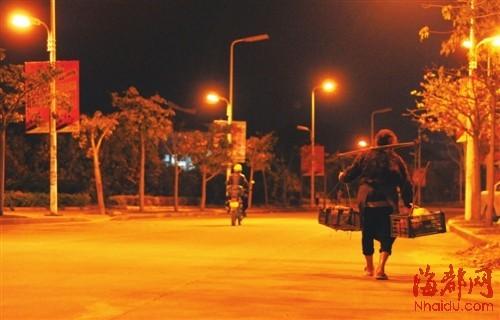每天卖完菜,依姆就挑着担子,默默走在回家的路上;路灯照映下,她的身影孤独但坚强