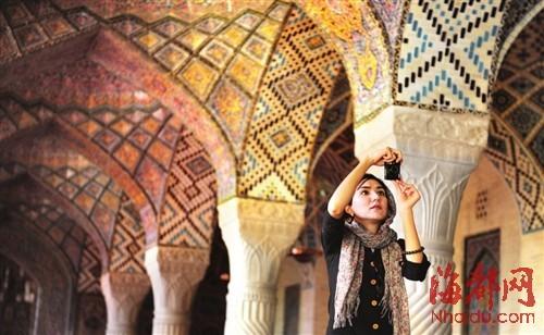 来自伊斯法罕的伊朗女大学生在安静祈祷后,拿出相机拍摄粉红清真寺独特之美