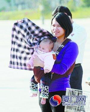 昨日我市天气晴好,图为一位女士为孩子遮挡阳光。(本报记者 姚凡 摄)