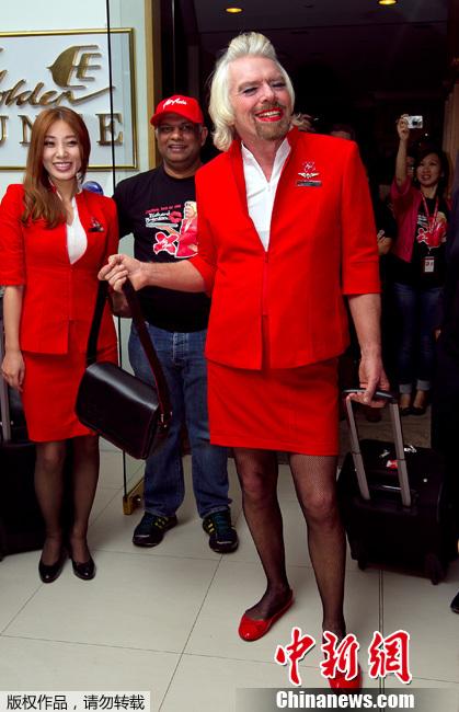 """英国亿万富翁理查德·布兰森与人打赌""""失败"""",打扮成空姐将为乘客服务。"""