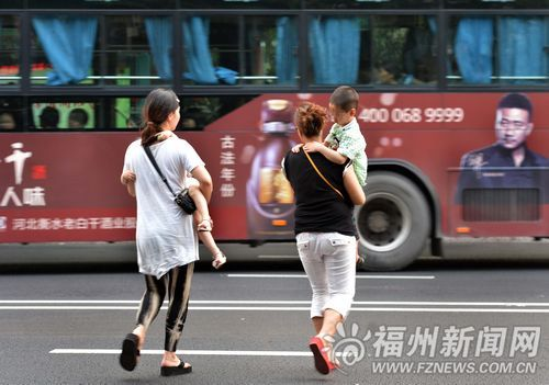 在白马路,两位家长抱着小孩一路小跑横穿马路。