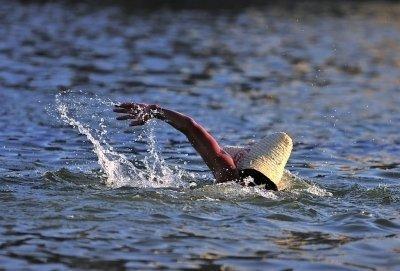 西河游泳场,一位市民戴着草帽在水中游泳。