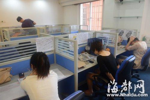 """警方捣毁的诈骗窝点内,""""秘书组""""在格子间内""""办公"""",桌上贴着台湾地图,还摆着多部电话及""""控台组""""准备的受害者资料(警方供图)"""