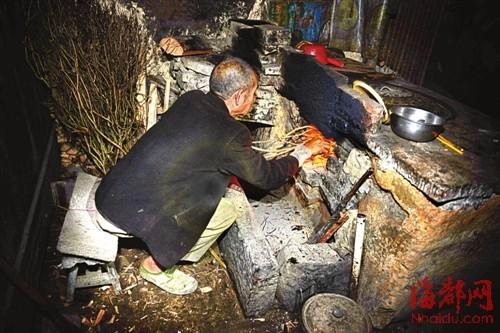 老人仅有的右手,就是他的眼睛,伸进灶膛里,﹃看看﹄火烧起来没有  感谢大闽网王龙志供图