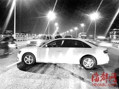 白色奥迪轮胎抱死,车道被占,车后是长长的车龙